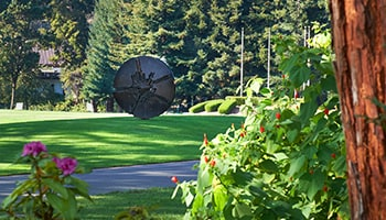 "On the grassy Holmegren Meadow, surrounded by trees and flowers, stands Arnaldo Pomodoro's modernist sculpture, ""Disco""."