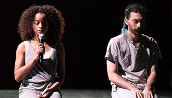 On a dark stage, two Mills student performers stand in the spotlight, eyes downcast, as one speaks into a microphone.